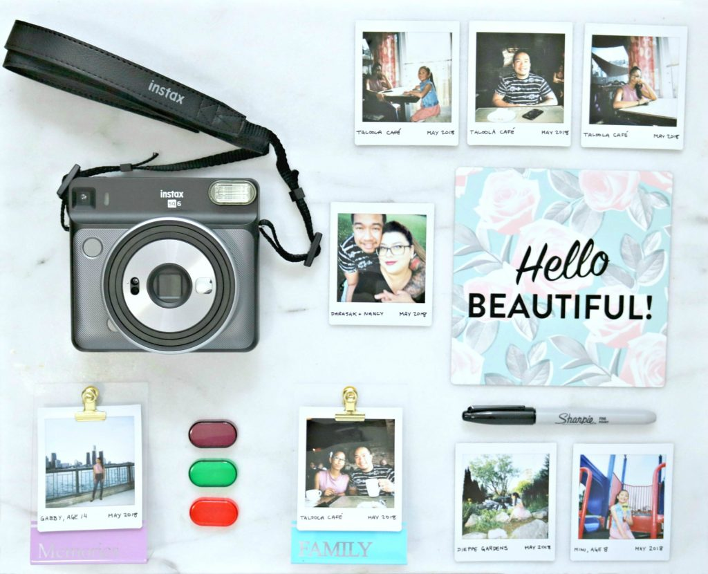 A flat lay of Instax prints, camera, sharpie and more.