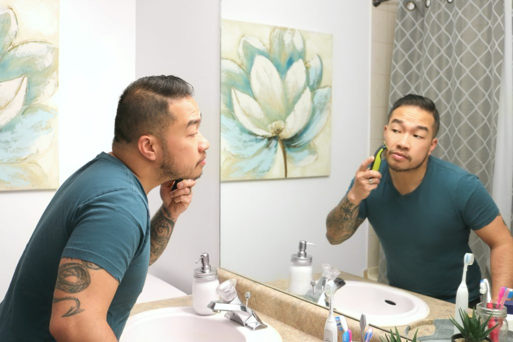 A man trips his beard in the reflection of the mirror.