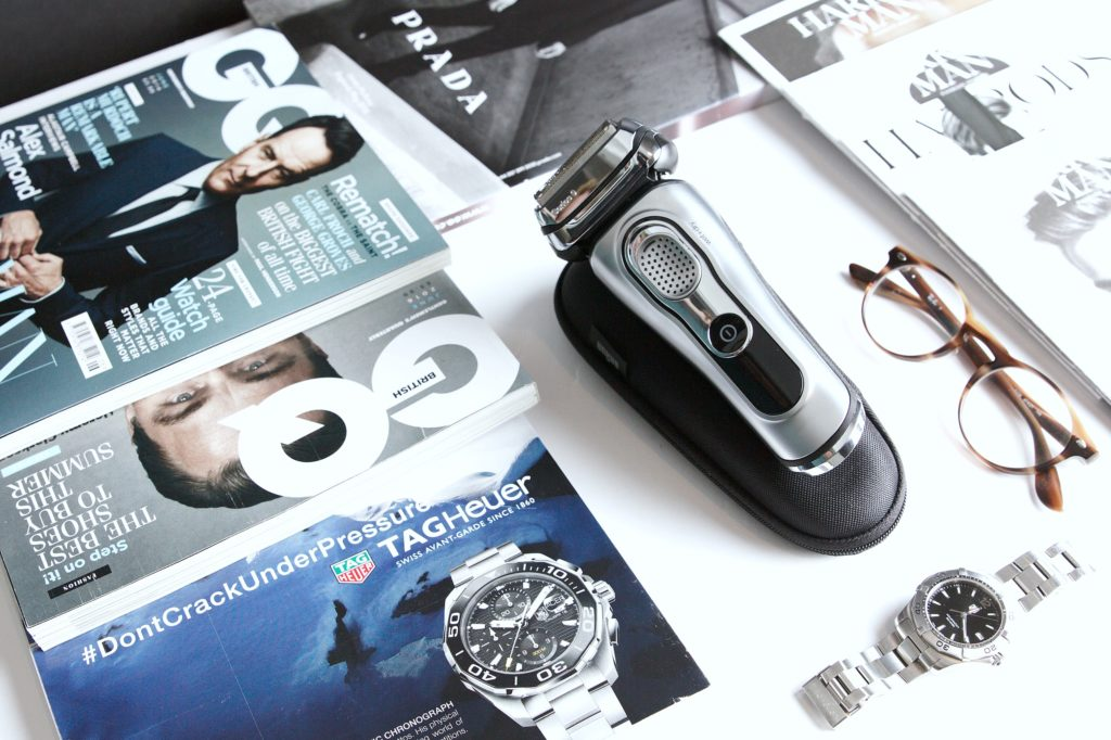 Razor surrounded by men's magazine, watch, and glasses.