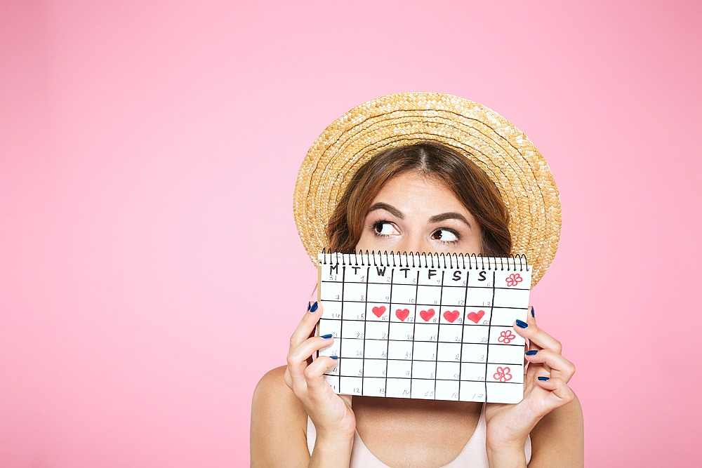Woman holds her menstrual cycle on a calendar in front of her face.