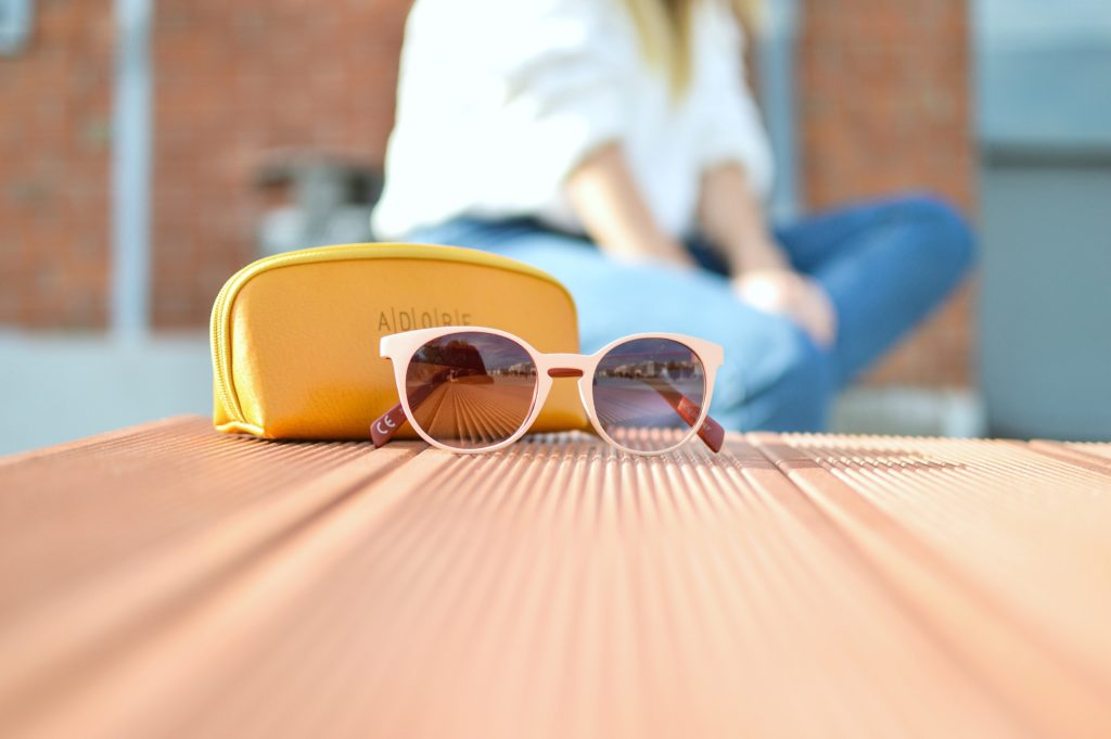 Woman sits in the background on a bench while a pair of sunglasses is the main focus.