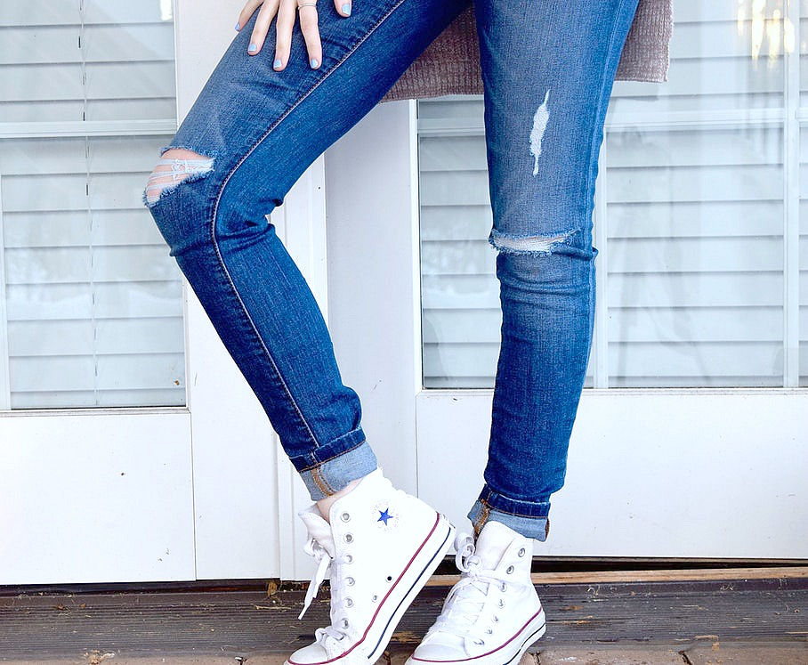 A woman stands in front of the door, only her lower half is visible, she is wearing sneakers.