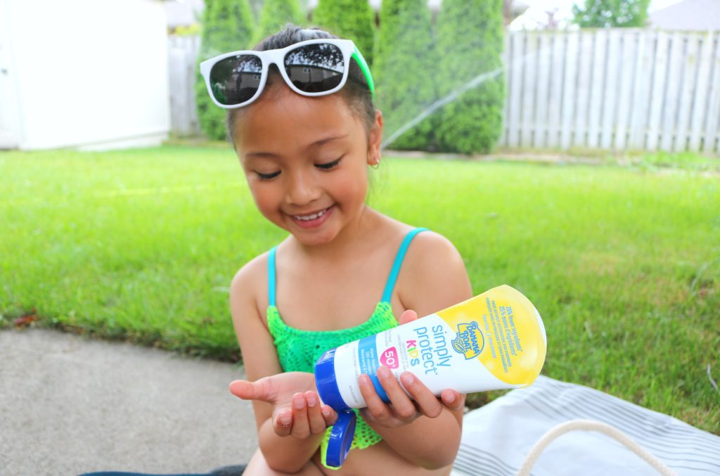 A little girl puts on sunscreen before playing in the sprinkler.
