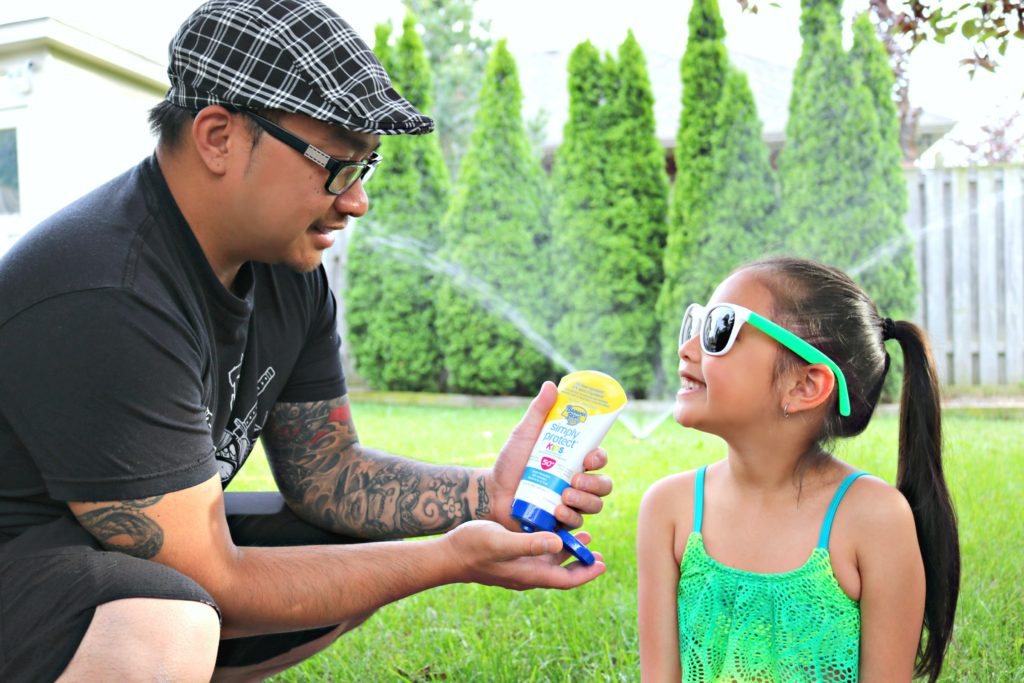 A little girl looks at her dad while applying Banana Boat Lotion sunscreen.