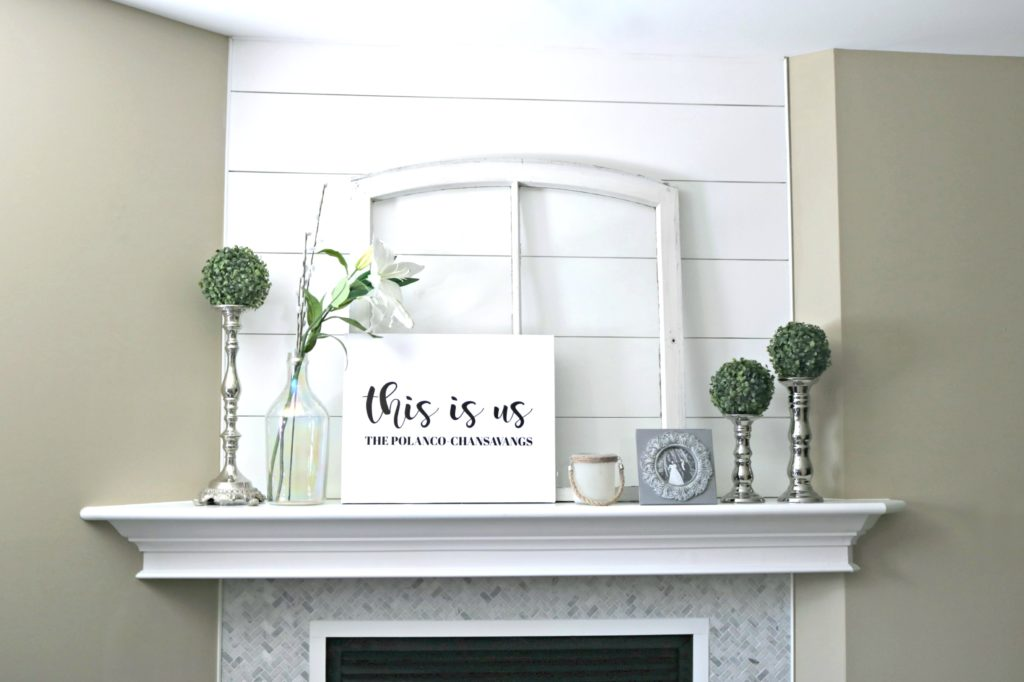 A mantle decorated with farmhouse rustic decor.