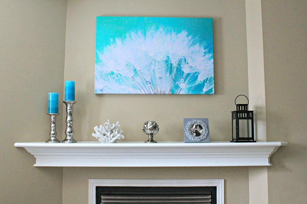 Mantle that is decorated with teal accents and very nautical decor.