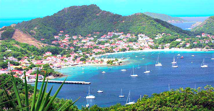 The beautiful bay of Guadeloupe is lined with sail boats.
