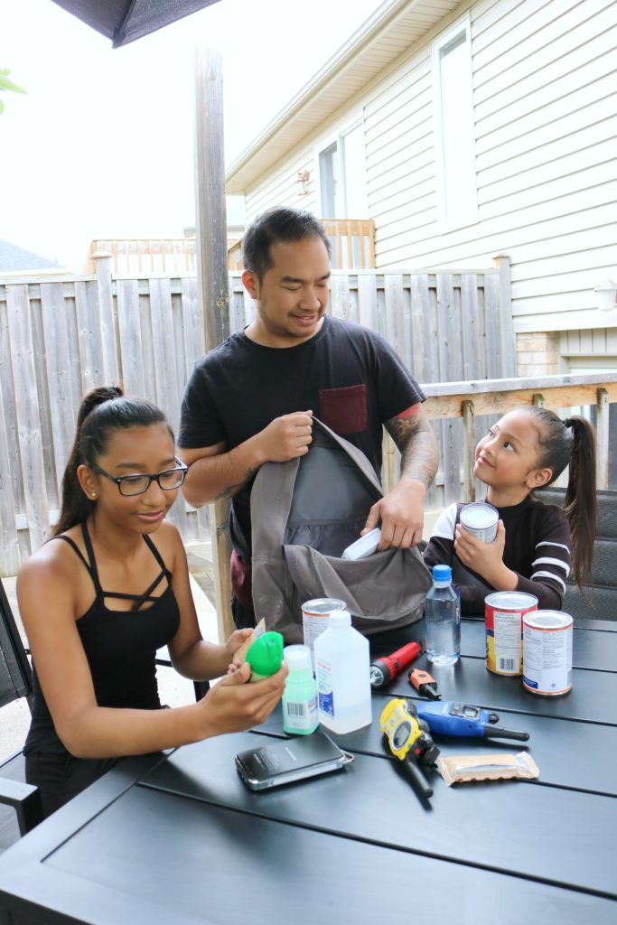 A family checks their emergency kit for expiration dates.
