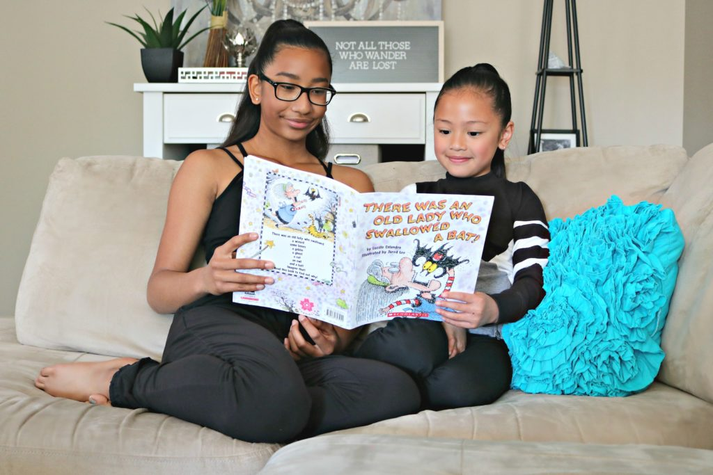 Two young girls read together in their living room.
