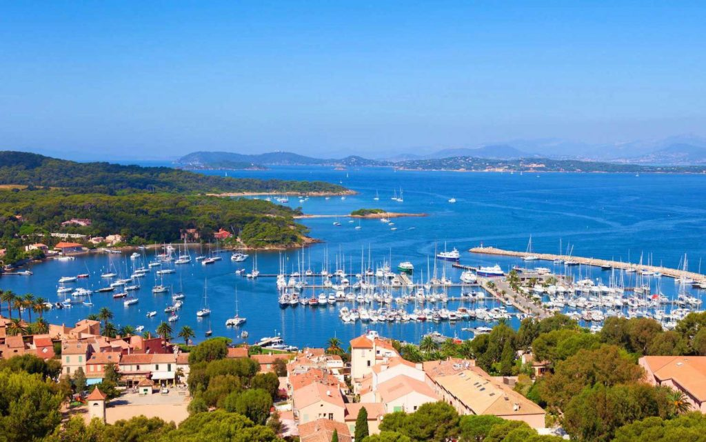 The island of Porquerolles is lined with sail boats and navy blue water.