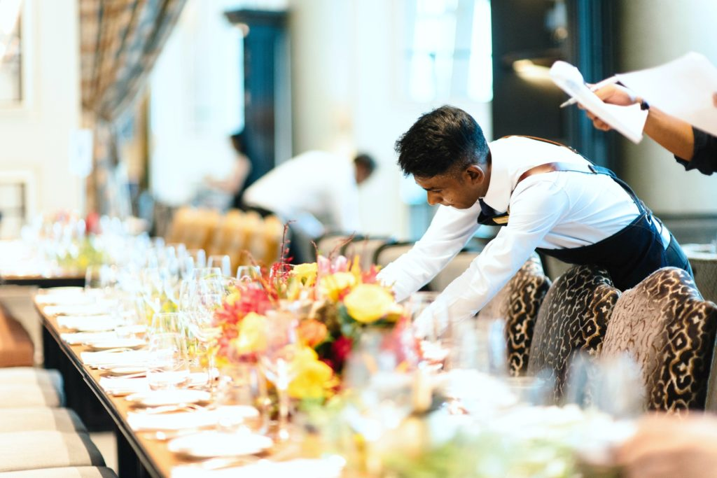 A caterer prepares the table at an event.
