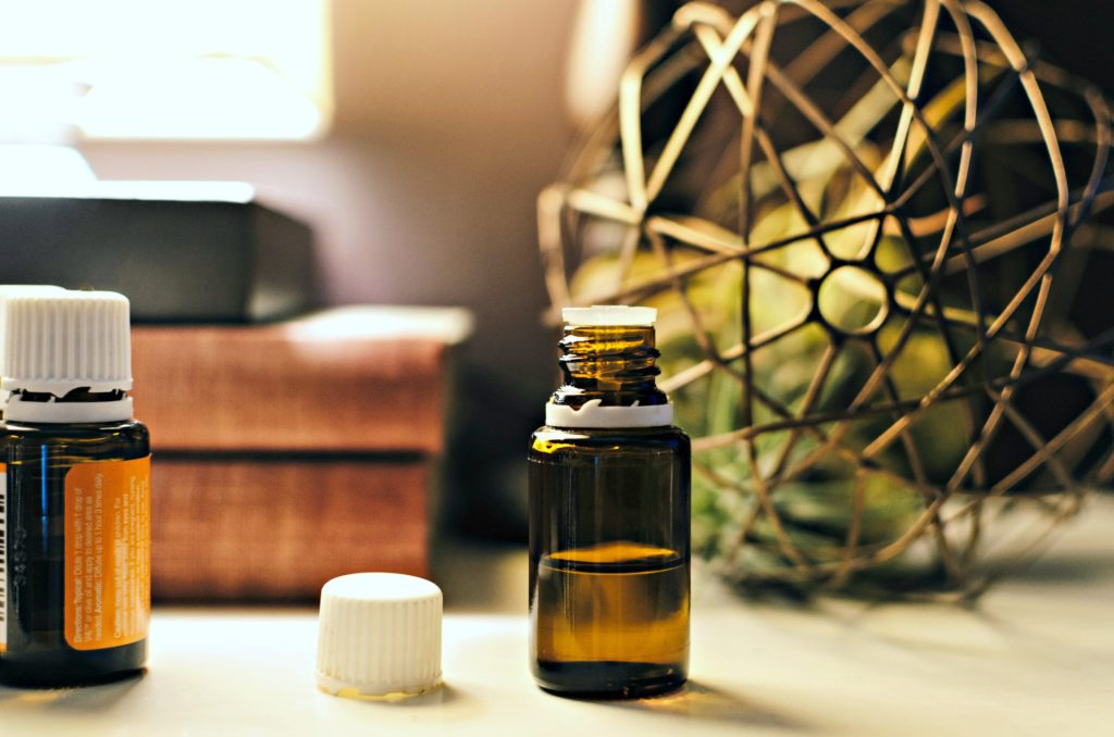 A vial of essential oils sits on a dresser.