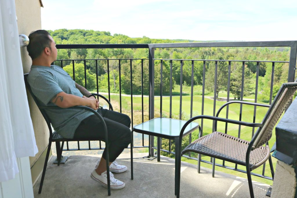 A man sits in a chair on the balcony of his Executive Suite.