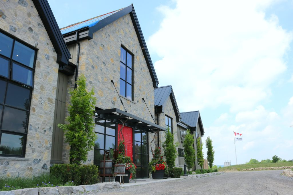 A side view of the winery, you can see the Canadian flag and Adamo flag flying in the background.