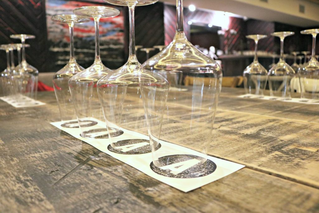 Wine glasses are lined up, ready to help customers sample Adamo wine.