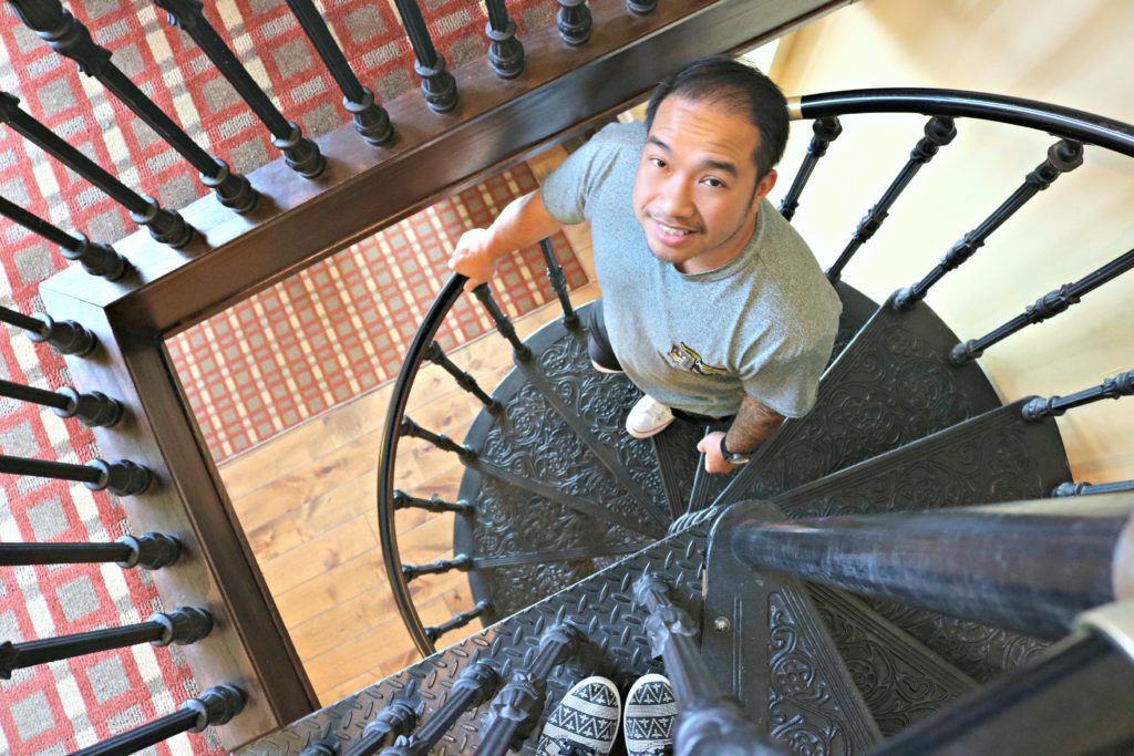 A man looks up at his wife while going down a spiral staircase. The wife's feet are pictured.