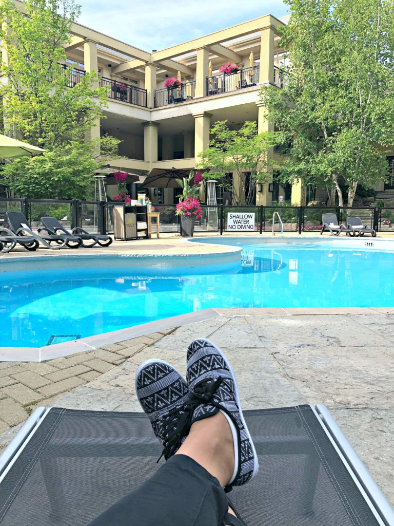 A woman sits in a patio chaise with her legs crossed, feet are visible, outlooking the gorgeous Hockley Valley Resort pool.