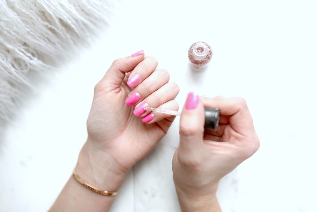 A woman does her nails and puts glitter polish on top of a pink nail polish.
