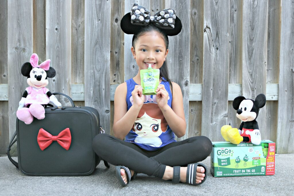 A little girl enjoys a GoGo SqueeZ with Mickey and Minnie with a box of GoGo SqueeZ with instructions on how to win a trip to Disney World.