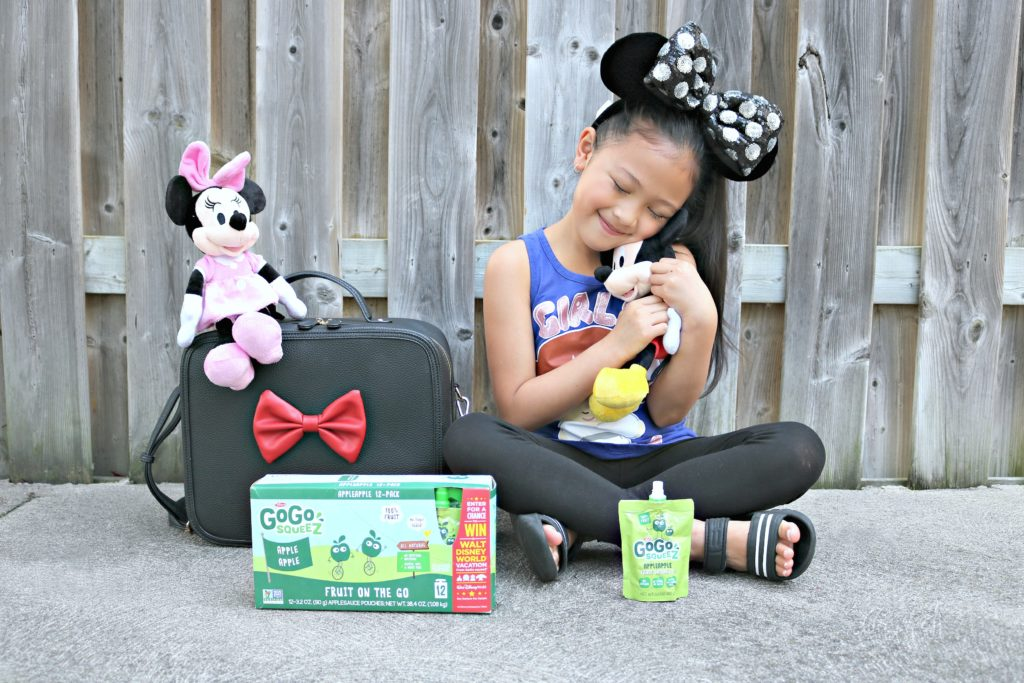 A little girl hugs Mickey Mouse and hopes to win a trip to Disney World with GoGo SqueeZ!