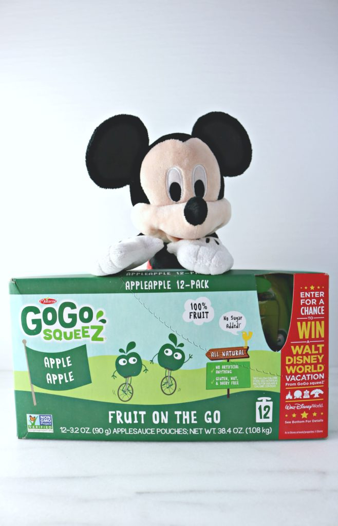Mickey stands behind a GoGo SqueeZ box with instructions on how to win a trip to Disney World.
