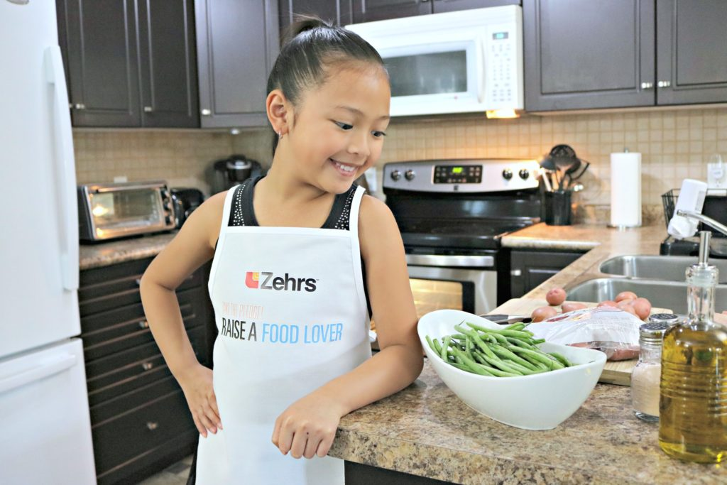 A little girl wears a Zehrs Take the Pledge - Raise a Food Lover apron and looks at her counter full of ingredients.