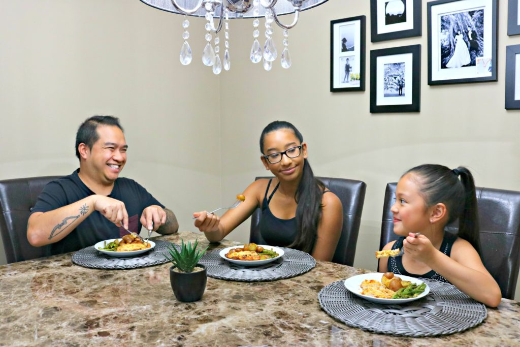 A family sits at the dinner table enjoying the one-pan parmesan garlic chicken dinner they just made.