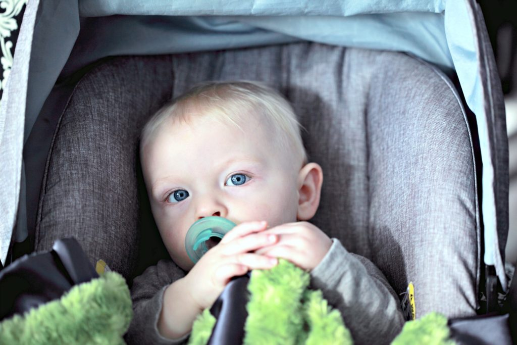 A baby sits in the good family car in their car seat.