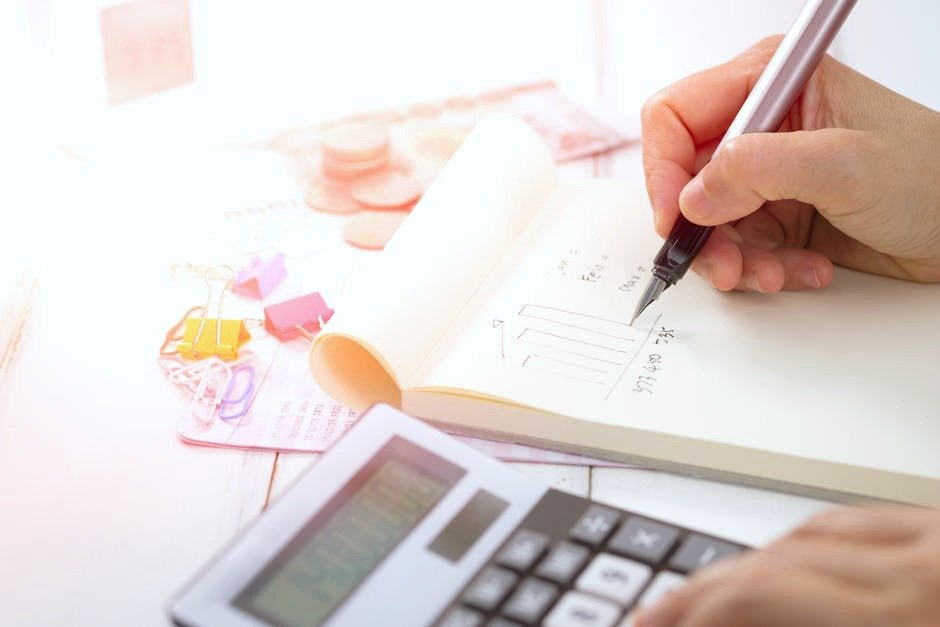 A person writes down a budget and a note pad, pen, and calculator is shown. They are writing down financial tips that help you save more.