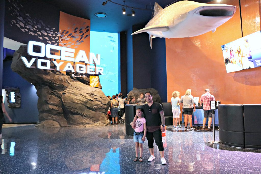 A girl and her dad stand in front of the Ocean Voyager section at the Georgia Aquarium.