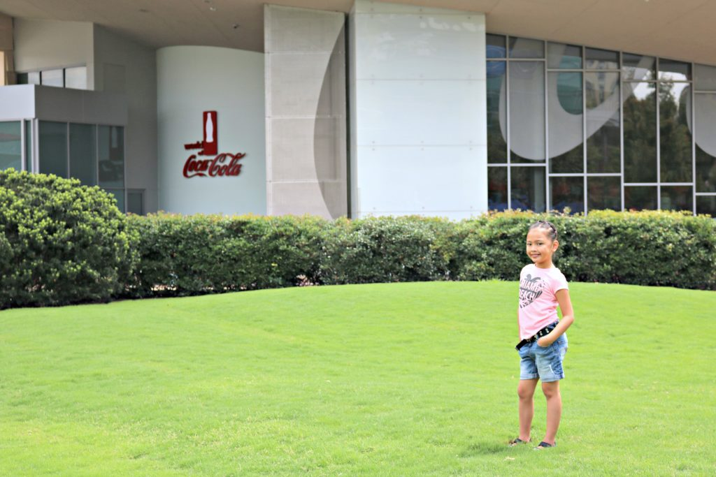 Little girl stands in front of the World of Coca-Cola.