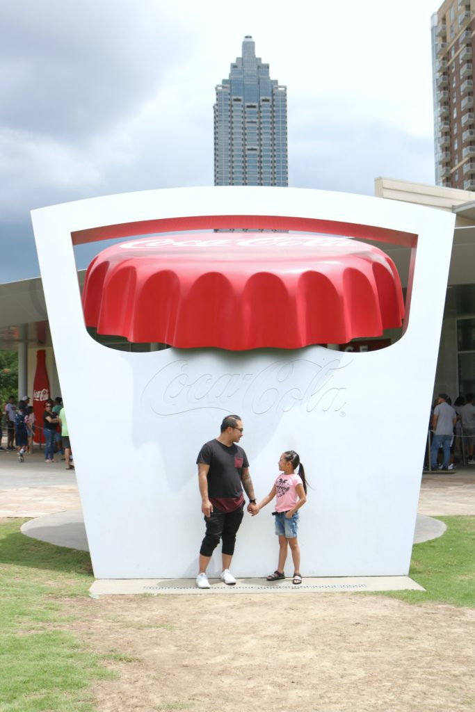 A little girl and her dad hold hands in front of the iconic bottle cap opener at World of Coca-Cola.