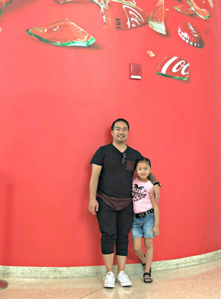 Little girl and her dad stand inside the World of Coca-Cola.