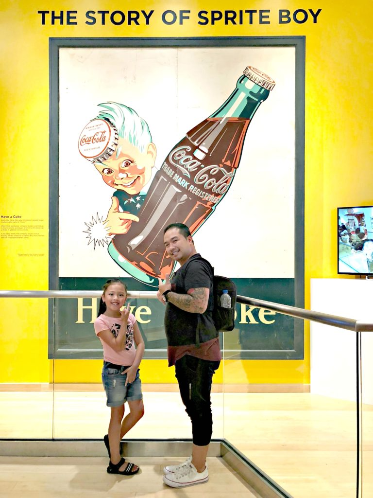 A father and his daughter stand in front of Sprite Boy sign at World of Coca-Cola.