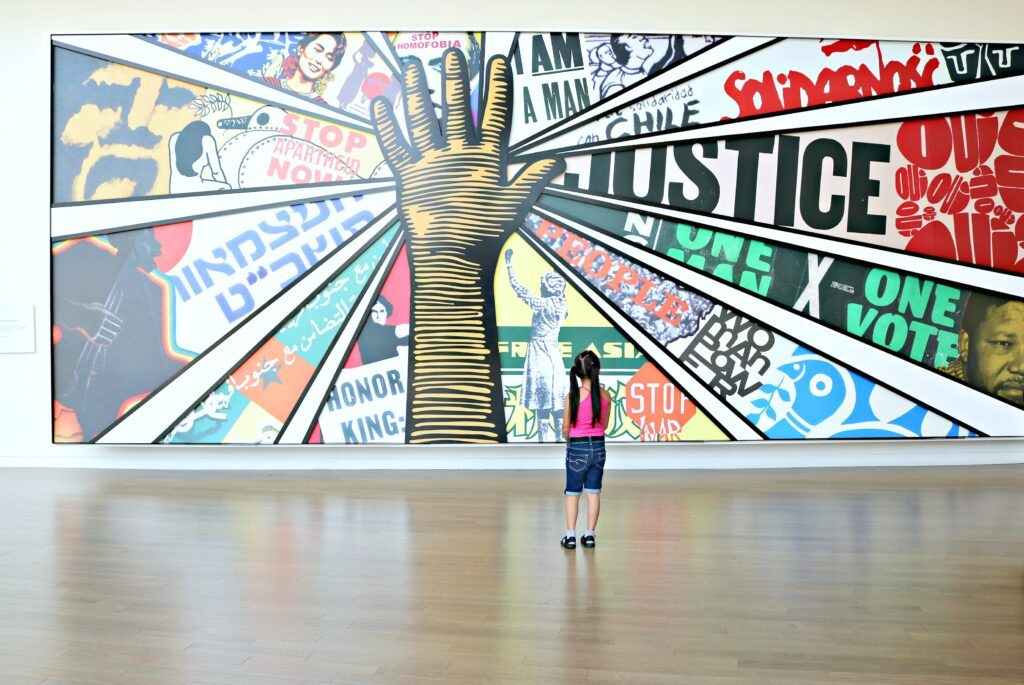 A little girl stands in front of a mural at the Center for Civil and Human Rights. One of many things to do in Atlanta.