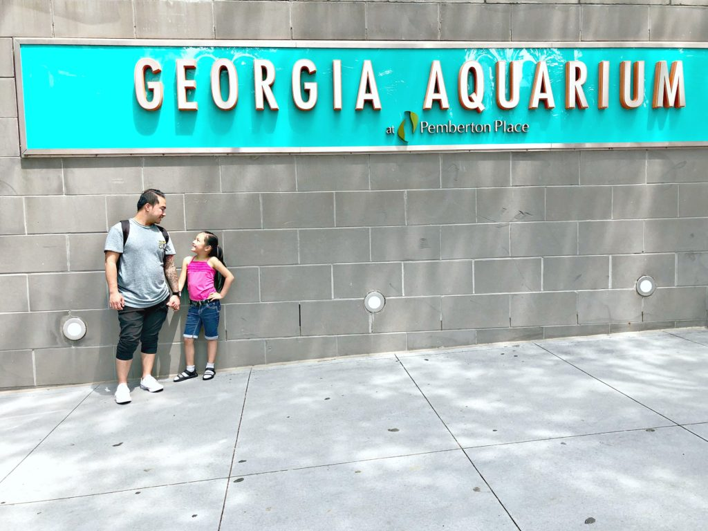A girl and her father stand in front of the Georgia Aquarium sign.