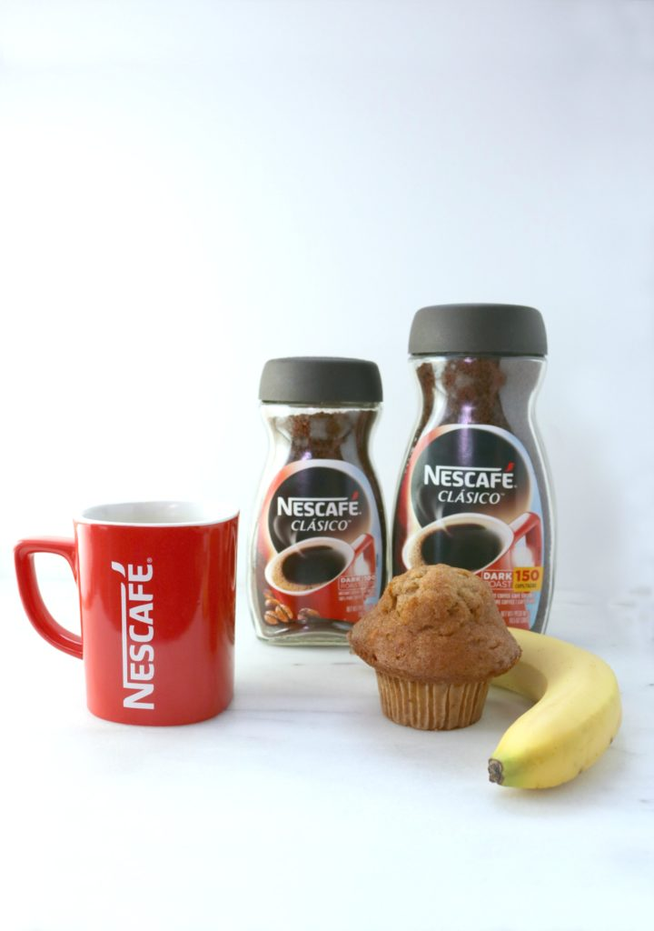 Two sizes of Nescafe Clasico are shown, served in a Nescafe red mug, a banana, and muffin.
