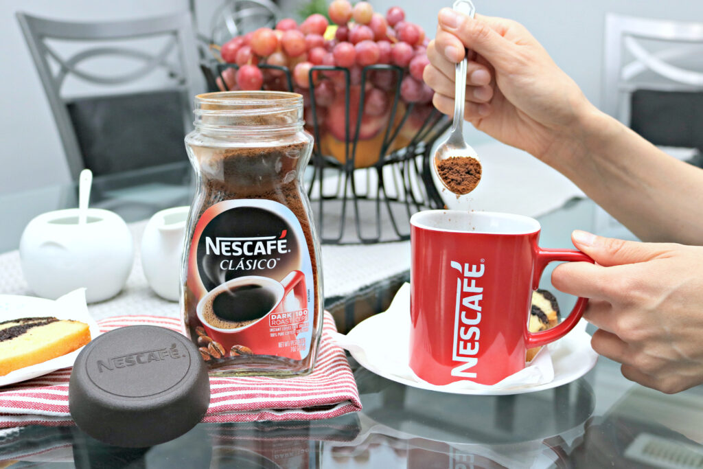 A woman prepares a cup of Nescafe Clasico.