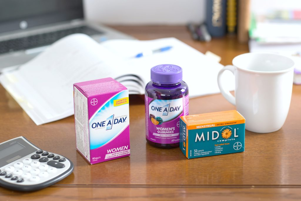 A computer desk is shown with One a Day vitamins and Midol.