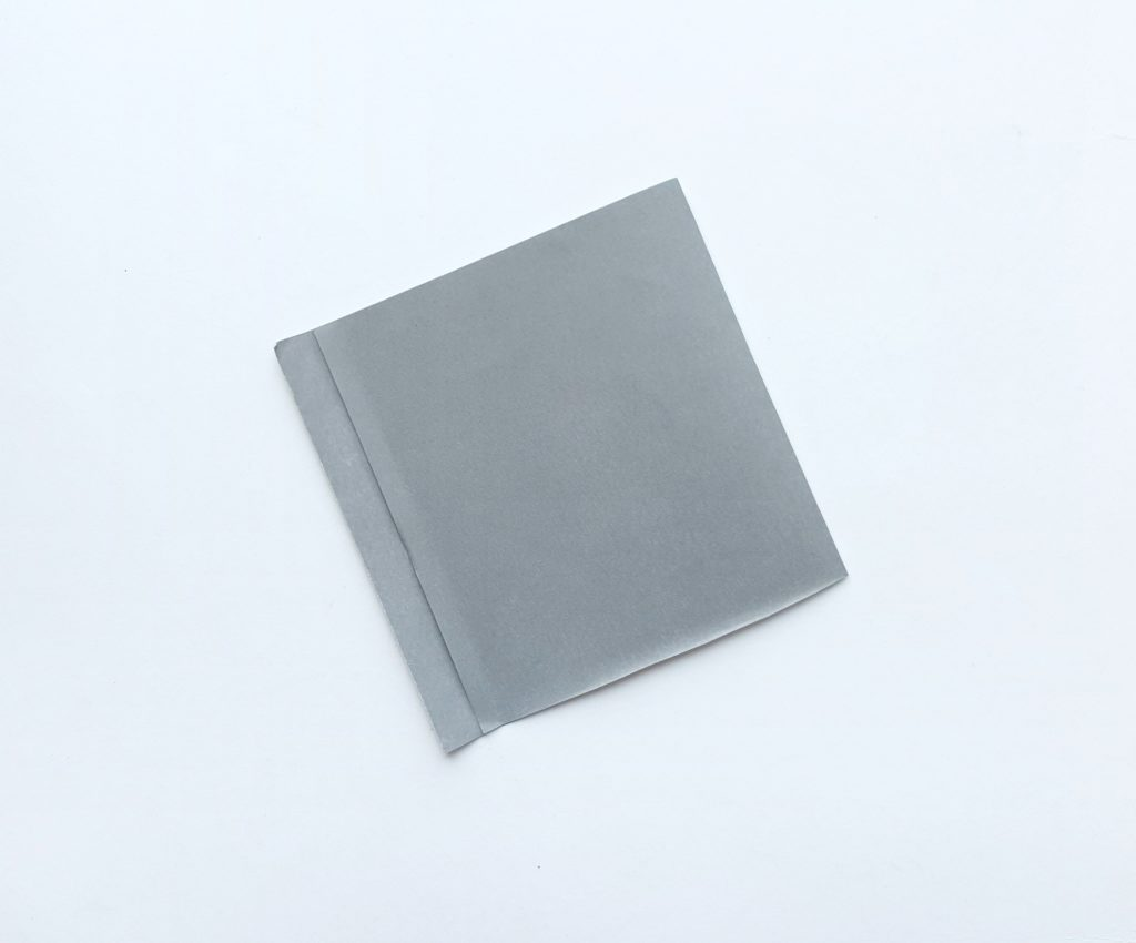 A grey piece of construction paper folded.