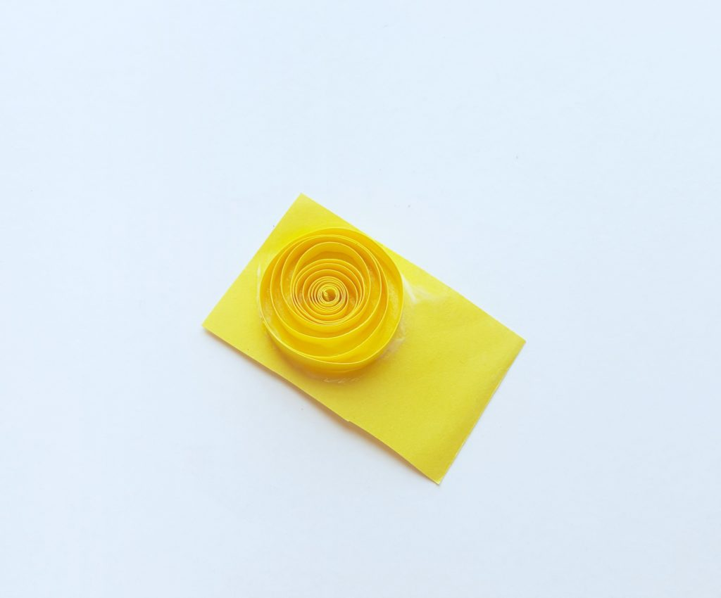 Quilled paper roll glued onto another piece of yellow paper.