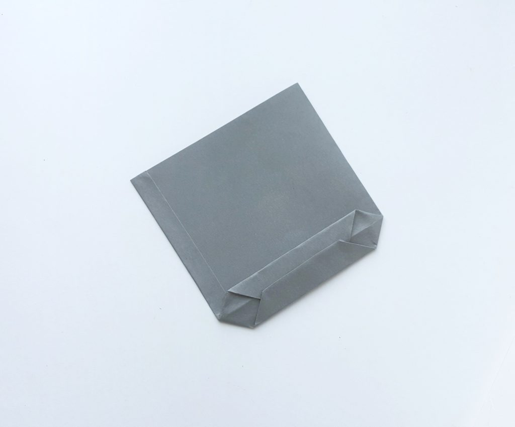 Grey paper being folded into a bag, the bottom is shown folded and almost secure.