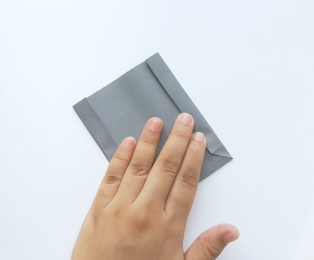 The same grey paper is folded inwards on both sides.