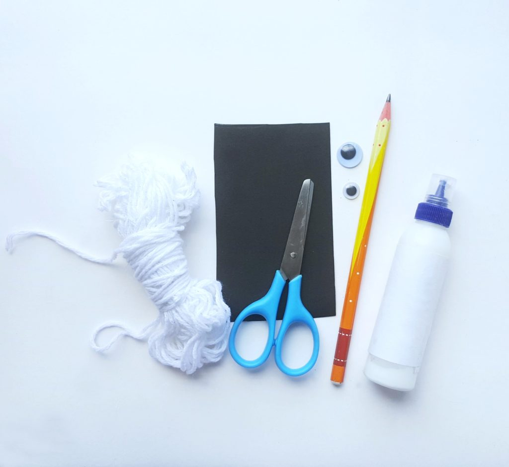 A group of supplies with black paper, scissors, yarn, pencil, googly eyes and glue.