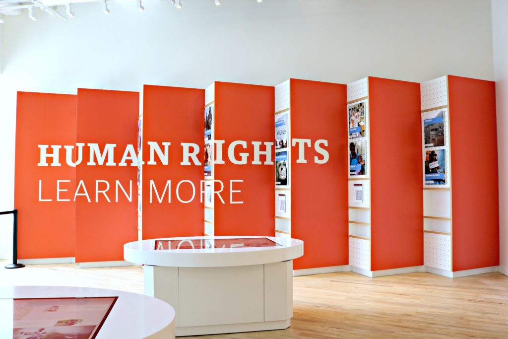 A sign reads: Human Rights, Learn More.
