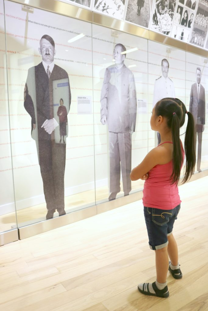 A little girls stands with her arms crossed while she learns about the world's most notorious dictators.
