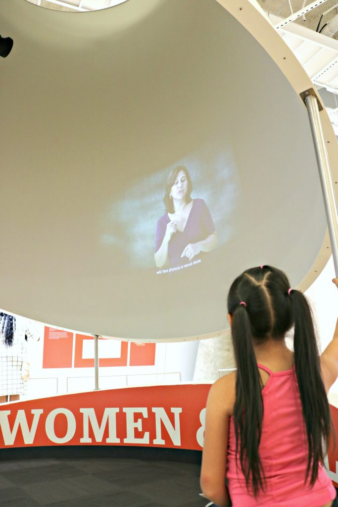 A little girl watches a video about women's rights at the Center for Civil and Human Rights.