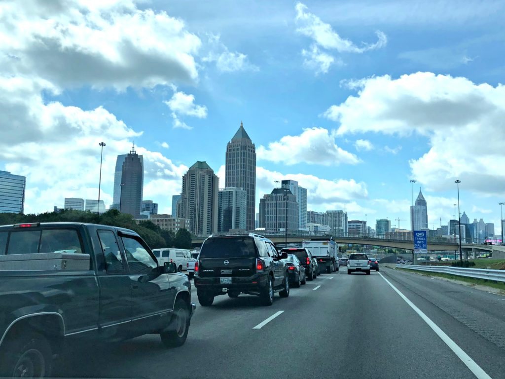Cars in traffic against the Atlanta skyline.