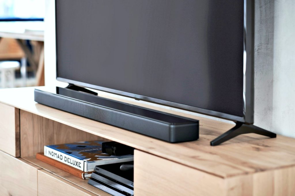 A Bose soundbar sits underneath a TV.