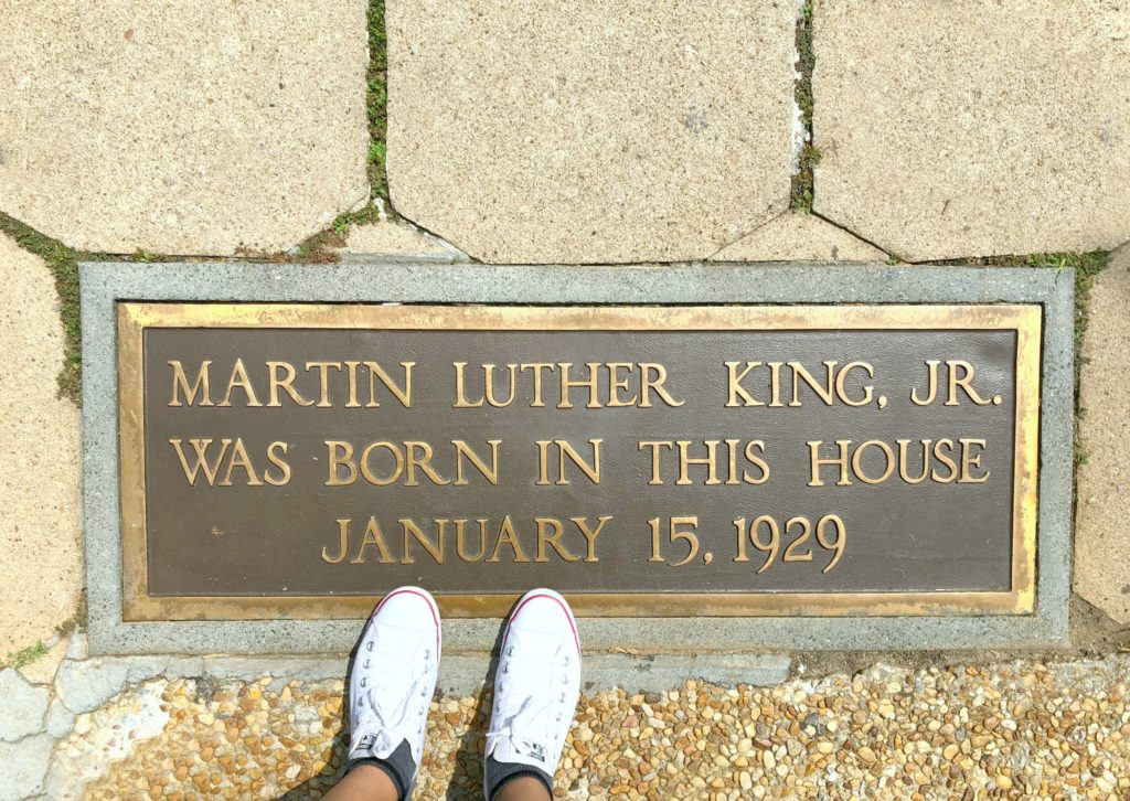 Feet are shown standing in front of MLK's childhood home and plaque naming it so.